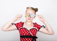 Stående av den lyckliga härliga unga flickan med söta candys iklädd nätt ung kvinna en röd klänning med den vita polkan Arkivfoto