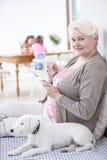 Stående av den lyckliga höga kvinnan som hemma använder den digitala minnestavlan vid hunden Arkivbild