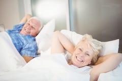 Stående av den lyckliga höga kvinnan som kopplar av förutom man på säng Royaltyfri Fotografi