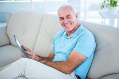 Stående av den lyckliga höga mannen som använder den digitala minnestavlan Arkivbild