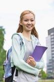 Stående av den lyckliga innehavboken för ung kvinna på högskolauniversitetsområdet arkivbild