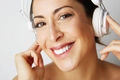 Stående av den lyckliga kalla flickan för mode avriven till midjan i vit hörlurar som lyssnar till musik över tom vit Arkivbild