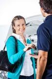 Stående av den lyckliga klienten som ger biltangenter till mekanikern Royaltyfri Foto