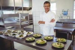 Stående av den lyckliga kocken med aptitretareplattor på beställningsstationen Arkivfoto