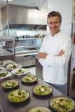 Stående av den lyckliga kocken med aptitretareplattor på beställningsstationen Royaltyfri Foto