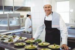 Stående av den lyckliga kocken med aptitretareplattor på beställningsstationen Fotografering för Bildbyråer
