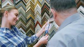 Stående av den lyckliga kunden som finner slutligen en ram för hennes bild i ramlager Arkivbild