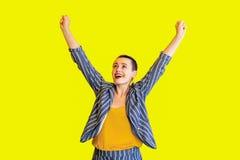 Stående av den lyckliga kvinnan för kort hår för förvånad vinnare unga härliga i gul skjorta och randigt dräktanseende för tillfä arkivfoton