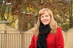 Stående av den lyckliga kvinnan i ett rött lag fall royaltyfri fotografi