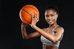 Stående av den lyckliga kvinnan i hållande basket för sportswear över svart fotografering för bildbyråer
