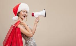 Stående av den lyckliga kvinnan i den santa hatten som rymmer röda shoppa påsar royaltyfri foto