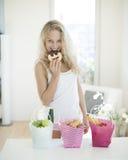 Stående av den lyckliga kvinnan som äter kakan på diskbänken Arkivbild