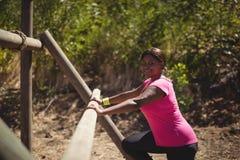 Stående av den lyckliga kvinnan som övar på utomhus- utrustning under hinderkurs royaltyfria bilder