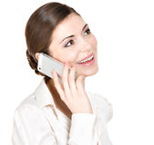 Stående av den lyckliga kvinnan som kallar vid mobil i vitskjorta Arkivfoto