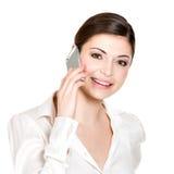 Stående av den lyckliga kvinnan som kallar vid mobil i vitskjorta Arkivbilder