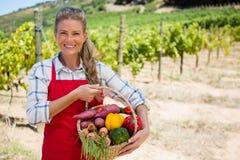 Stående av den lyckliga kvinnan som rymmer en korg av nya grönsaker Royaltyfri Fotografi