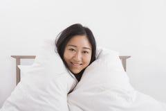 Stående av den lyckliga kvinnan som slås in i täcke på säng Royaltyfria Foton