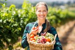 Stående av den lyckliga kvinnliga bonden som rymmer en korg av grönsaker arkivfoton