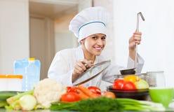 Stående av den lyckliga kvinnliga kocken arkivfoton