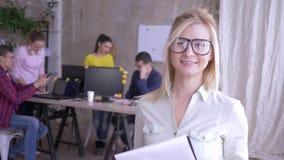 Stående av den lyckliga kvinnliga kontorsarbetaren i exponeringsglas som tar anmärkningar på papper och ler därefter på kameran stock video
