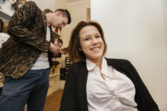 Stående av den lyckliga kvinnliga kunden som får frisyr i skönhetsalong Royaltyfria Bilder