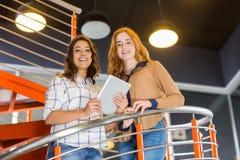 Stående av den lyckliga kvinnliga ledaren som använder den digitala minnestavlan på trappuppgång arkivbilder