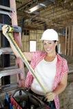 Stående av den lyckliga kvinnliga leverantören med att mäta bandet på konstruktionsplatsen royaltyfri bild