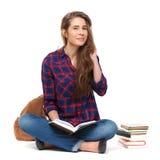 Stående av den lyckliga kvinnliga studenten som läser en isolerad bok Arkivfoton