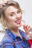 Stående av den lyckliga le Caucasian blonda kvinnan i kontrollerad skjorta som dricker röd fruktsaft Arkivfoton