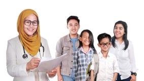 Stående av den lyckliga le kvinnliga asiatiska muslim doktorn för förtroende med den unga familjen, sjukvård och medicinskt sjukf royaltyfria foton