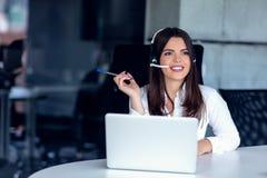 Stående av den lyckliga le kvinnliga operatören för telefon för kundservice på arbetsplatsen royaltyfria foton