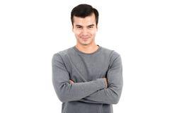 Stående av den lyckliga le mannen som bär den tillfälliga gråa t-skjortan som korsar hans armar Arkivbilder