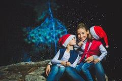 Stående av den lyckliga le unga kvinnan och gulligt kidboy med tomtebloss som utomhus firar jul med det dekorerade trädet Arkivfoton