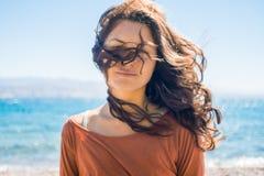 Stående av den lyckliga le unga kvinnan på strand- och havsbakgrund Vindlekar med långt hår för flicka Arkivbilder