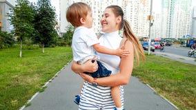 Stående av den lyckliga le unga kvinnan som kramar hennes litet barnson och går på stadsgatan arkivfoton
