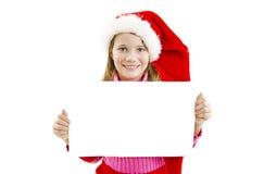 Stående av den lyckliga lilla flickan i jultomtenhatt med vitmellanrumsbrädet royaltyfri bild