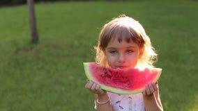 Stående av den lyckliga lilla flickan med vattenmelon i sommar Sunny Park lager videofilmer