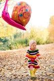 Stående av den lyckliga lilla flickan som spelar med luftballongen i parkera Royaltyfria Foton