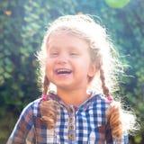 Stående av den lyckliga lilla skratta flickan med råttsvansar arkivfoto