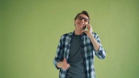 Stående av den lyckliga manliga studenten som talar på mobiltelefonen som gör en gest och ler stock video