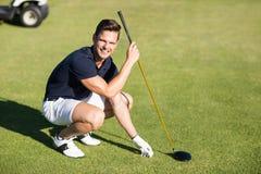 Stående av den lyckliga mannen som förlägger golfboll på utslagsplats royaltyfri foto