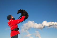 Stående av den lyckliga mannen som rymmer hans vänhund på den soliga ängen i vinter arkivfoto