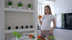 Stående av den lyckliga moderskapkvinnan med den stora buken som dricker fruktsaft för ny frukt under sund lunch på kokkonst i lä lager videofilmer