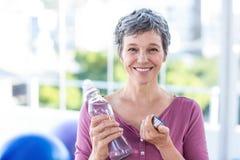 Stående av den lyckliga mogna kvinnan med vattenflaskan royaltyfri fotografi