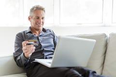 Stående av den lyckliga mogna mannen som använder bärbara datorn som ligger på soffan i hus royaltyfria bilder