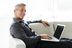 Stående av den lyckliga mogna mannen som använder bärbara datorn som ligger på soffan i hus royaltyfri foto
