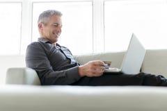 Stående av den lyckliga mogna mannen som använder bärbara datorn som ligger på soffan i hus fotografering för bildbyråer