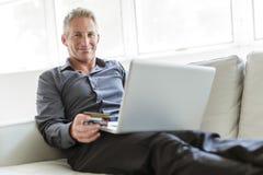 Stående av den lyckliga mogna mannen som använder bärbara datorn som ligger på soffan i hus arkivfoton