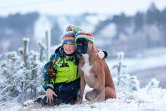 Stående av den lyckliga pojken med hunden i hatt Fotografering för Bildbyråer