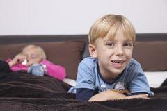 Stående av den lyckliga pojken med systern som sover på säng Arkivfoton
